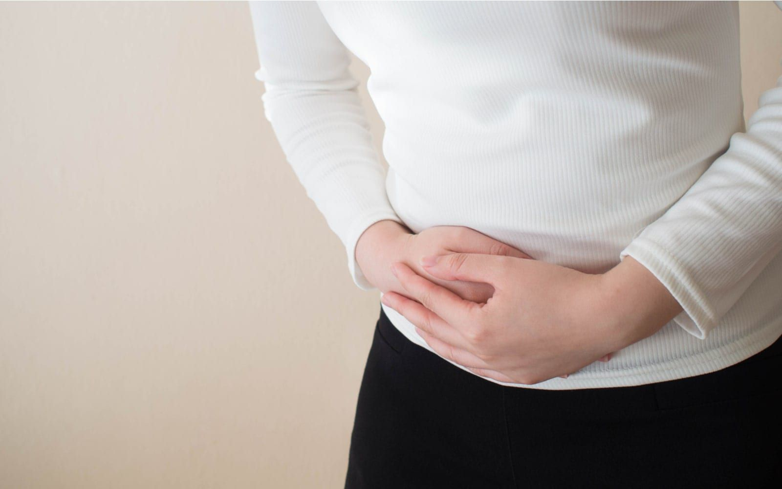 Woman clutching abdomen in pain from cysts